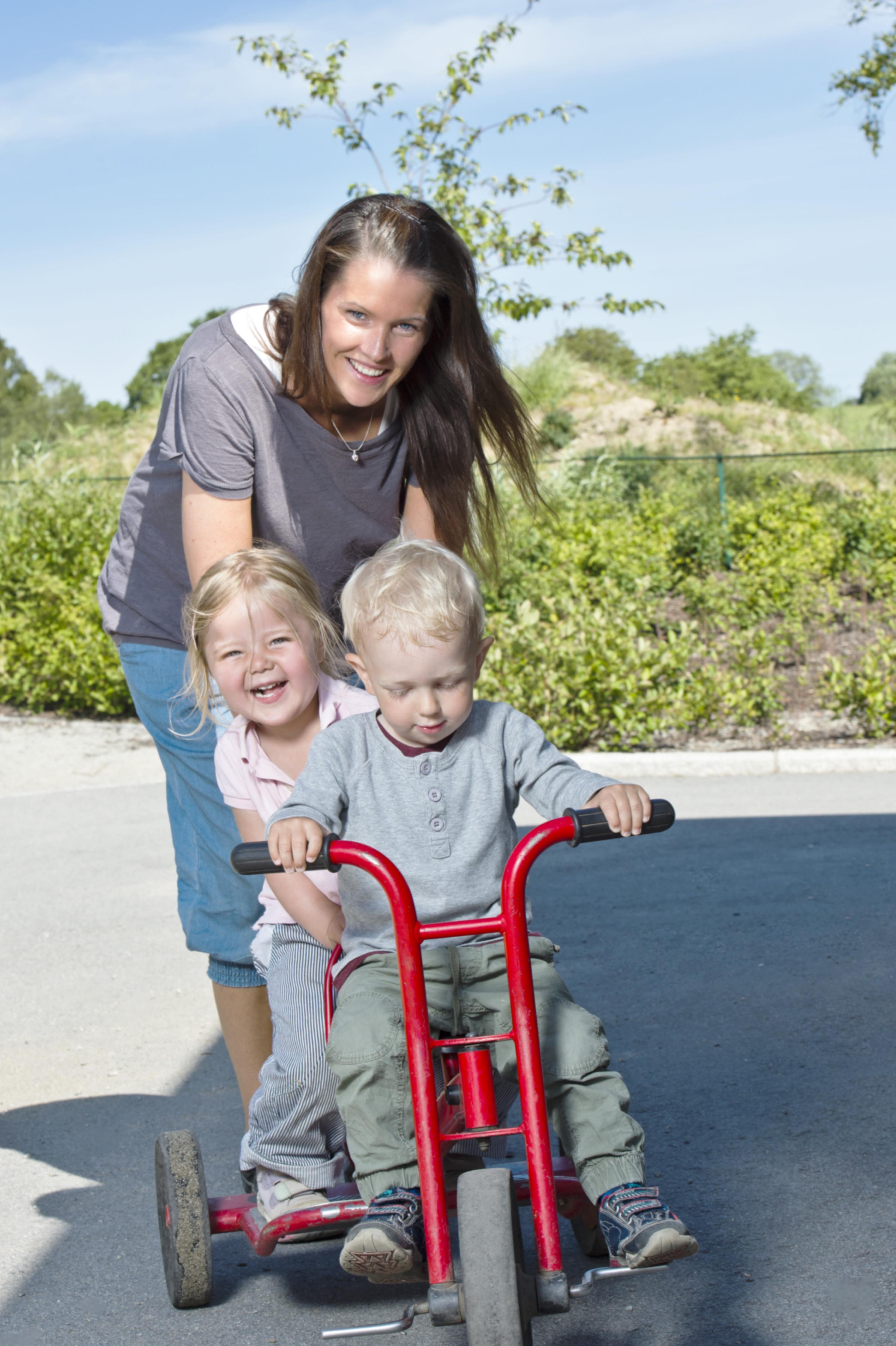 Kvinnelig barnehageansatt skyver på en pike på trehjulssykkel i solskinnsvær