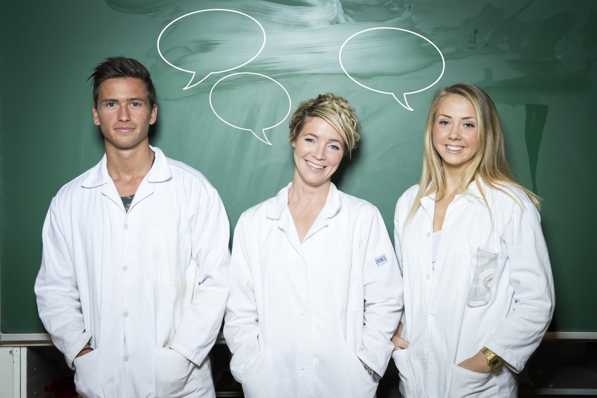 Realfagslærer står foran en tavle med to elever i labfrakker