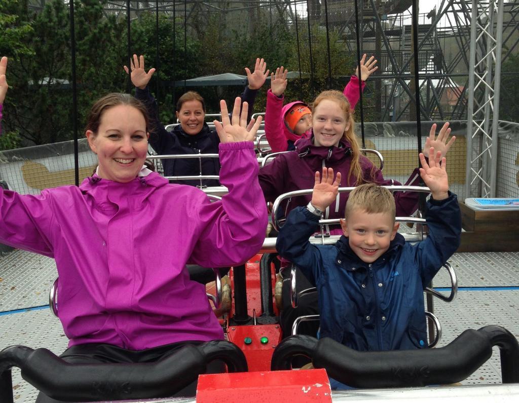 To voksne damer og tre barn sitter i berg- og dalbane-vogn med hendene i været.