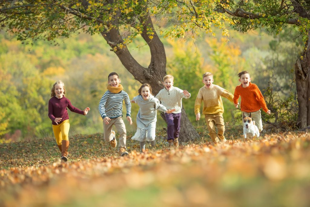 Fem barn i fargerike klær løper mot kamera på en eng med høstblader