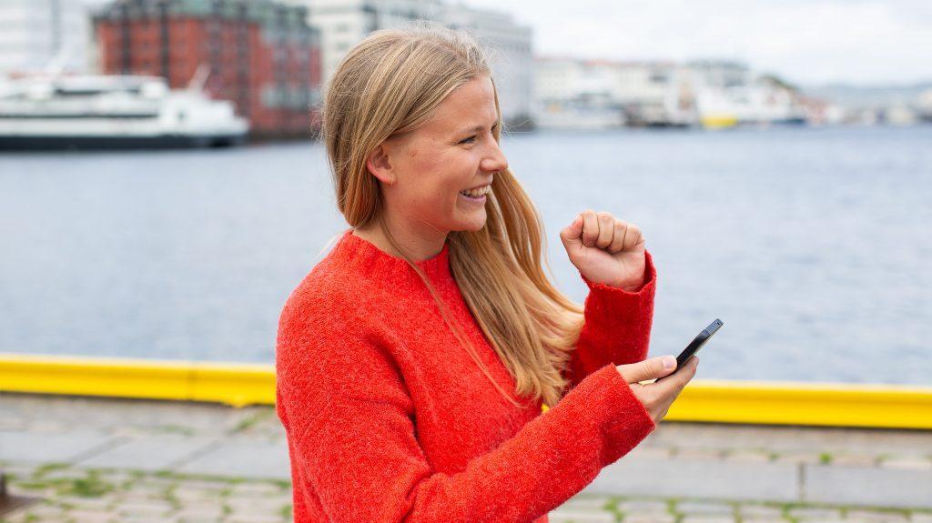 """Ung, blid jente med blondt hår og oransje genser står utendørs med telefon i hånden og knytter neven som et tegn på """"score""""."""