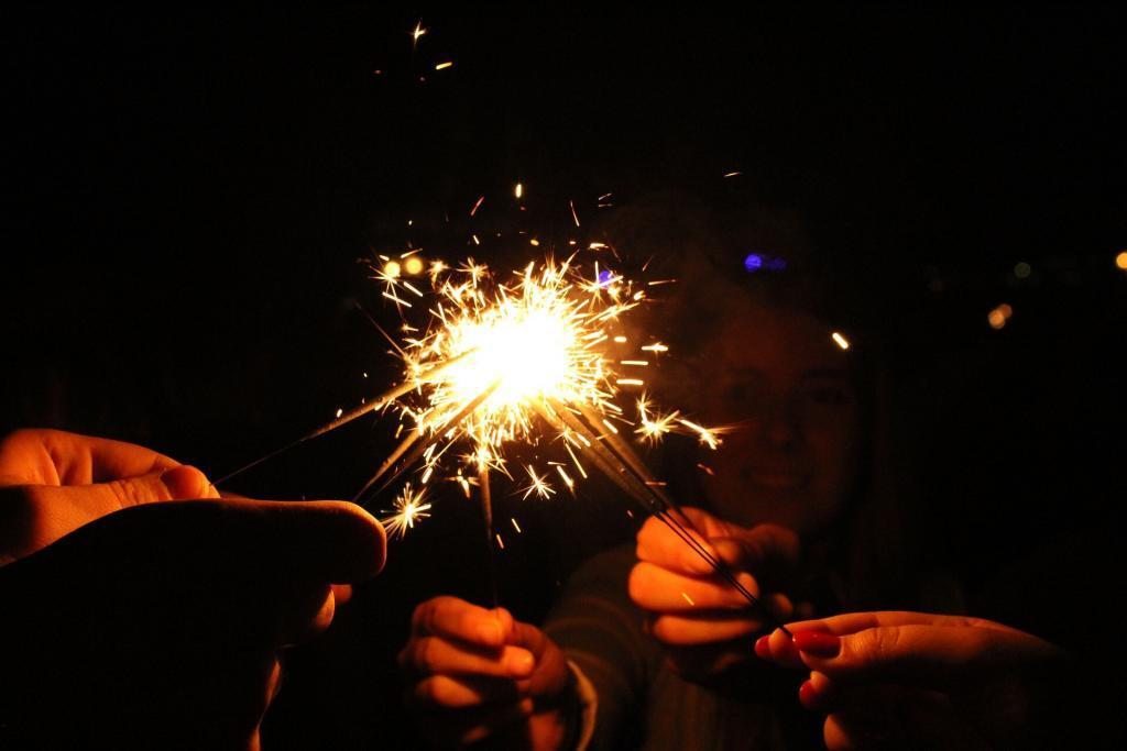 Fem mennesker holder og tenner hverandres stjerneskudd. Mørkt bilde, nesten kun hendene synes.