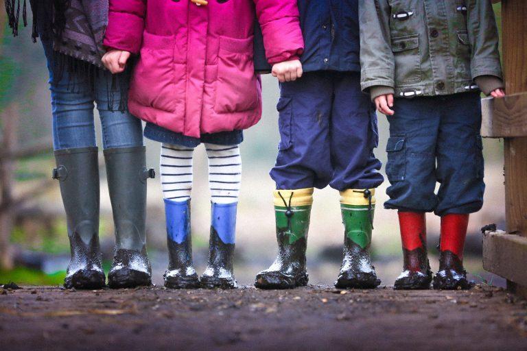 Fire barn fra livet og ned i uteklær og sølete støvler