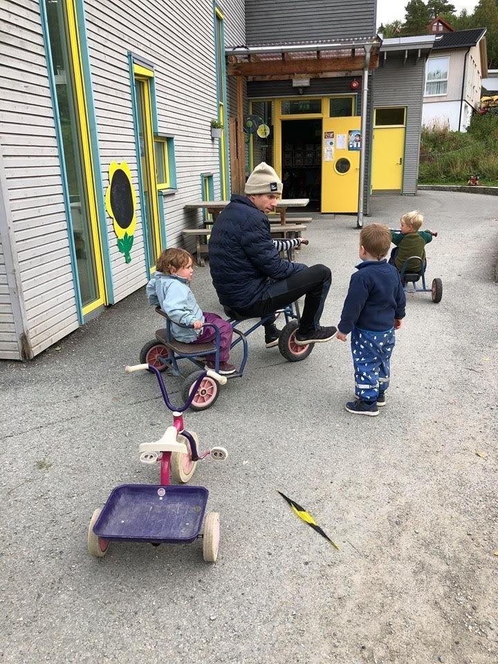 Halvor Egner Granerud sykler trehjulssykkel med et barn bakpå og prater med et annet barn som står foran han.