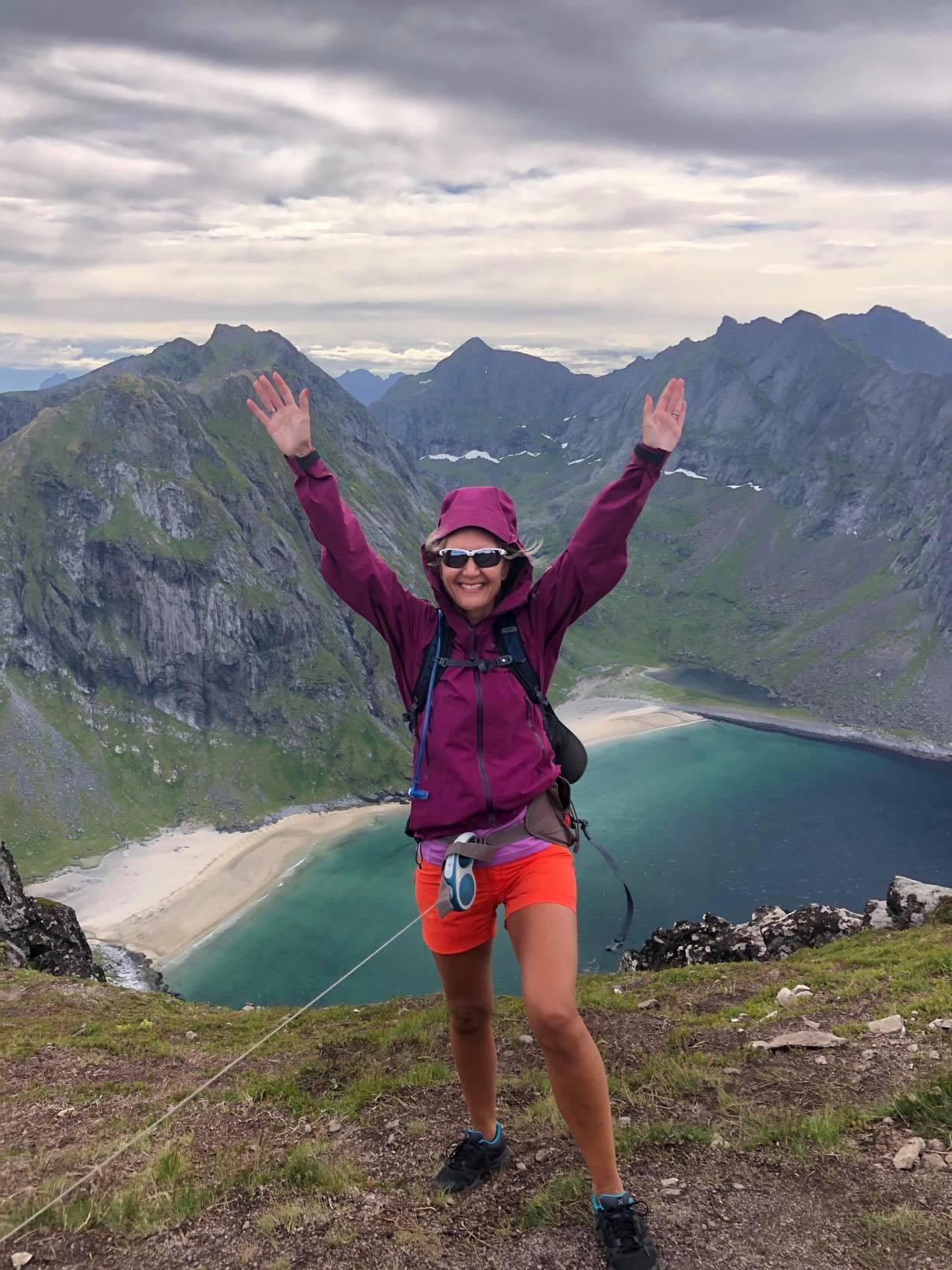 Hilde står i lilla jakke og shorts på toppen av et fjell i shorts og solbriller. I bakgrunnen er det storslått utsikt over fjell og strandlinje