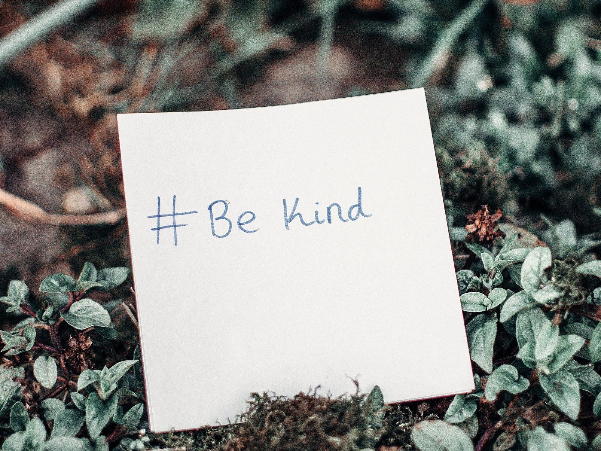 Post-it lapp på skogbunnen med #Be Kind.