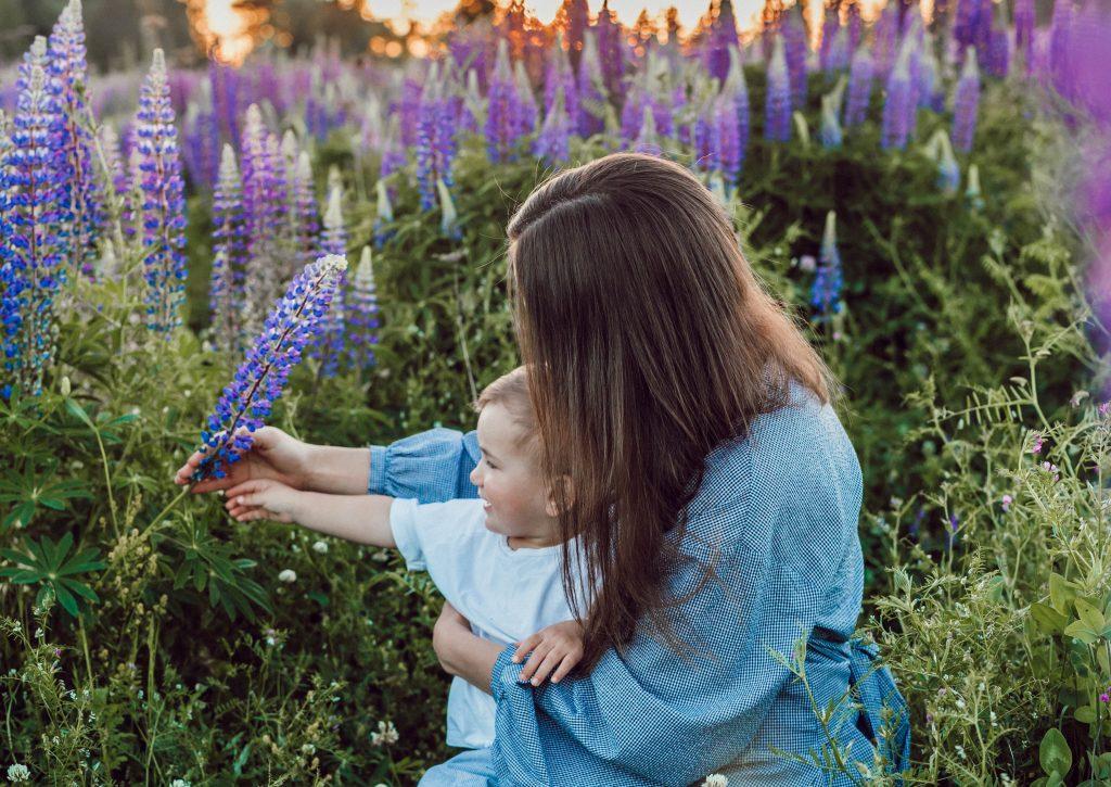 Ung kvinne med langt brunt hår sitter i en eng med et barn på fanget og utforsker de lilla blomstene sammen.
